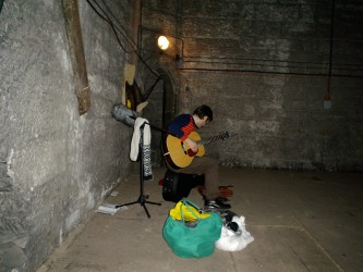 Neil sitting down near a wall of a bell tower holding a guitar