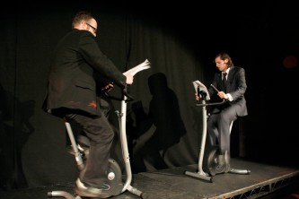 Two men in suits reading papers on stage, while riding exercise bikes