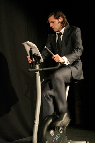 A man on an exercise bike reads from a paper, his hair is long