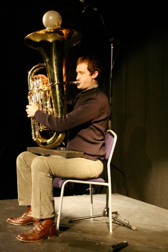 Robin Hayward sits whilst playing a tuba with a ball of sand at the horn