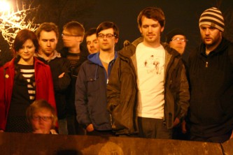 A crowd gathers around a skip by streetlight