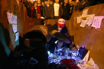 Two members of Usurper in a skip perform whilst audience overlooks