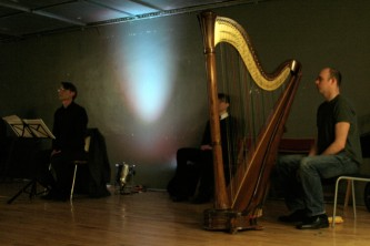 Rhodri Davies sits next to a large harp, others sit quietly