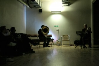 in the distance in a windowless room a tuba player and a trombone player play