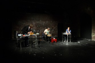 Three men in a railway arch perform with diverse instruments and noise apparatus