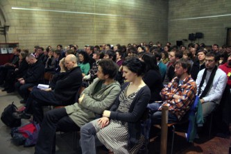 A large audience sits in a church space