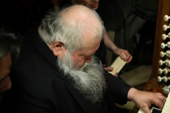 A bald and beared Hermann Nitsch looks down as he plays the organ