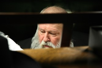 Hermann Nitsch with a big grey beard looks down, see though a music stand