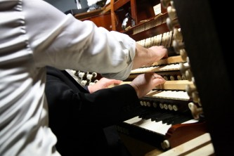 A tangle of shirted arms and arms play at an organ keyboard