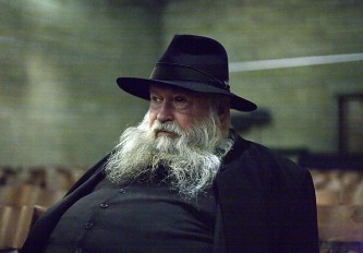 Herman Nitsch in a large hat and black button jacket with a grey beard