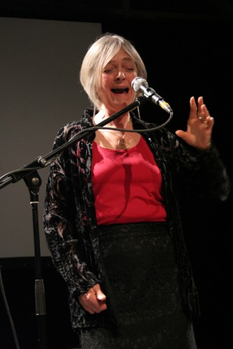 Joan La Barbara sings mouth open, eyes closed, hand up