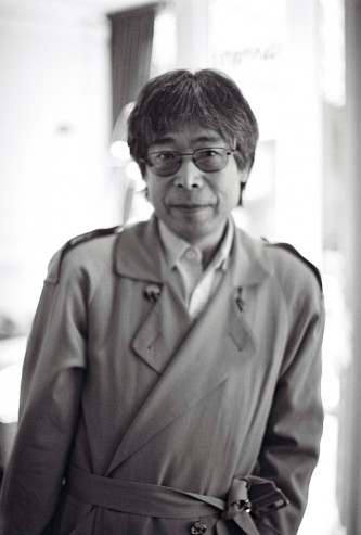 Tamio Shiraishi in a mac and glasses poses for a portrait