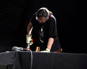 Nikos Veliotis braces himself as he drills at an object on table