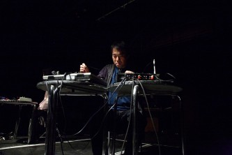 Otomo Yoshihide sits at two silver tables playing electronics