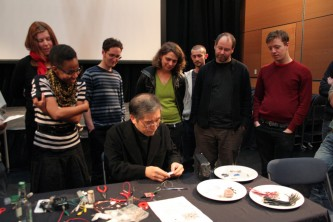 A group gather to watch Tetsuo Kogawa make a radio