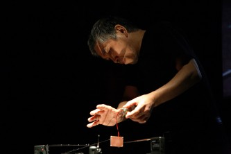 Tetsuo Kogawa holds a little electronic device in a magnetic field