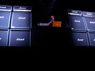 Rioji Ikeda operating a laptop surrounded by Marshall amplifiers
