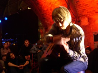 A man playing a guitar with audience in the background