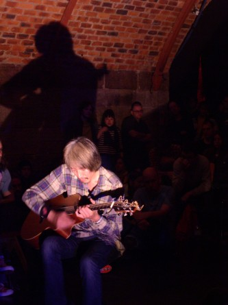 Man playing guitar in an arched room with light from below
