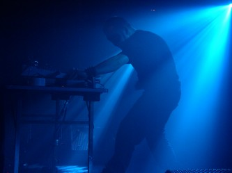 A man wearing a cat woman mask operates electrical music equipment in blue light