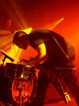 a man leans over a snare drum