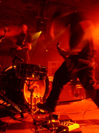 Two guitarists move while playing in orange light
