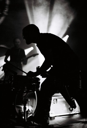 silhouettes of musicians bent in concentration