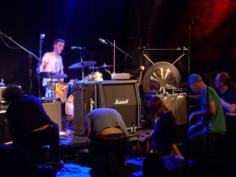 Several performers face amplifiers while a drummer sings