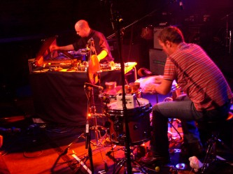 Two men touching carefully a harp and a floor tom in orange light