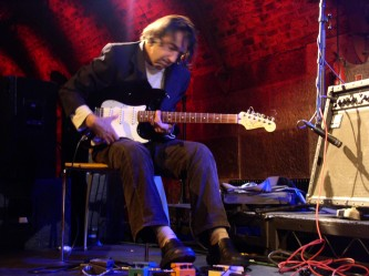 Loren Connors playing an electric guitar, with foot pedals