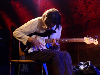 A man plays an electric guitar, his jacket now removed and lying nearby
