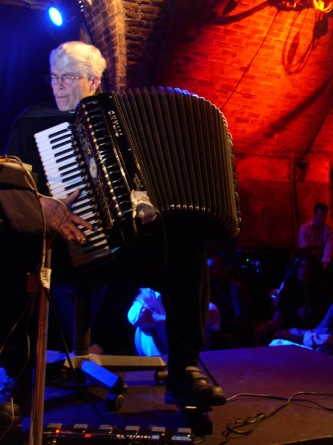 Pauline Oliveros playing an accordion whilst operating a foot pedal