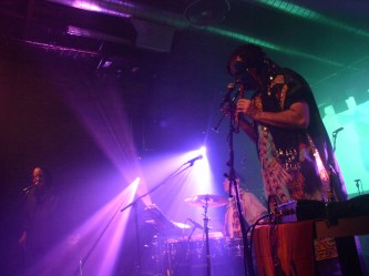 A masked performer blows a wind instrument in purple light