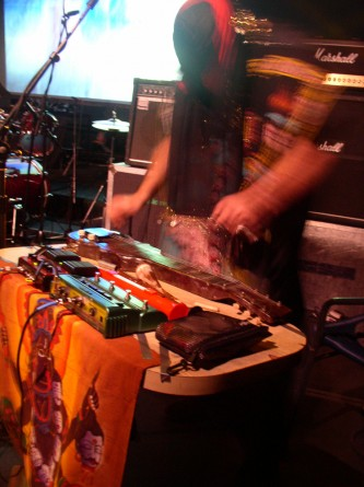 a masked figure hunches over a pedal steel guitar and other musical equipment