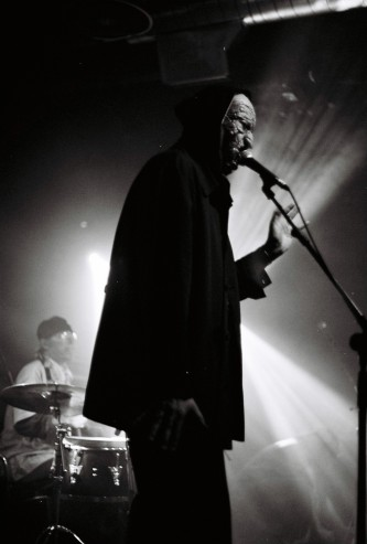 In the foreground a masked figure, drummer to rear