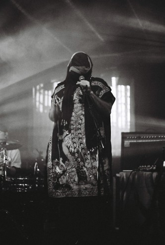 masked figure singing into a microphone