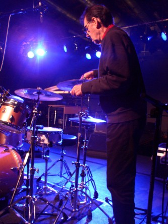 A man approaches a drum kit holding a cymbal