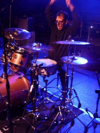 Tom Bruno holds his arms up above a drum kit