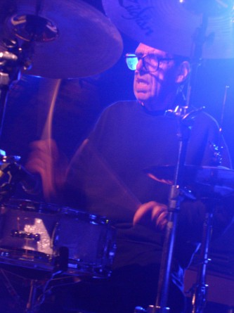 A man's face framed by cymbals