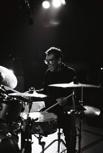 Tom Bruno lit from above plays the drums
