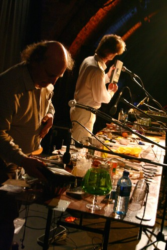two men, a cassette player held to a microphone, many objects on a table