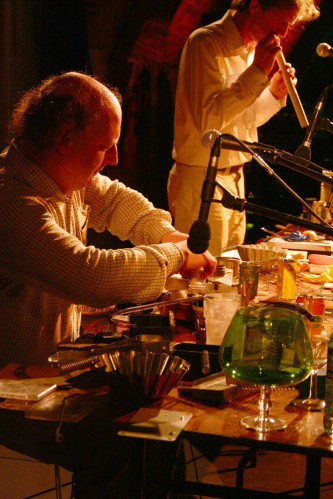 Two men at a table covered in objects, one blows a flute of some kind