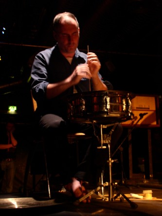 Sean Meehan plays a cymbal on a drum head with a dowel rod