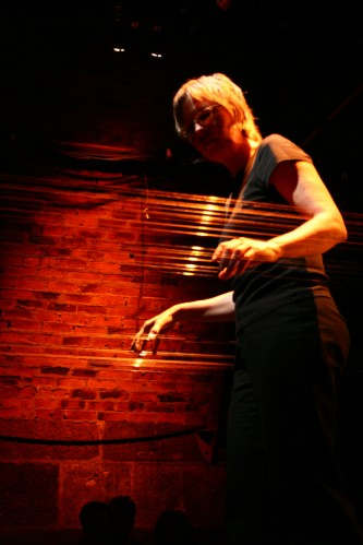 Ellen Fullman standing in a web of strings her hands on the strings