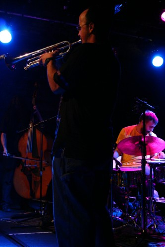 A man playing a trumpet with a drummer in the background