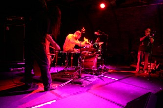 Eye Contact group on stage in pink light, bass, drums, trumpet left to right