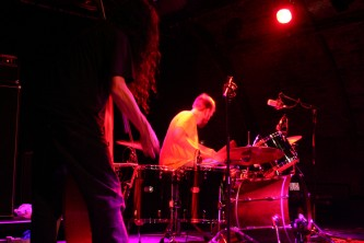 Double bass and drums left to right with pink light