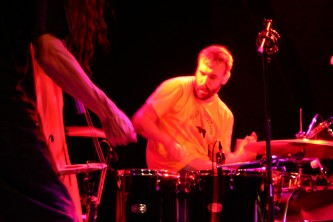 Double bass on left, drummer in centre of frame, pink light