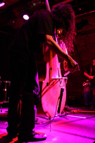 Close up of double bass being played by man with long hair