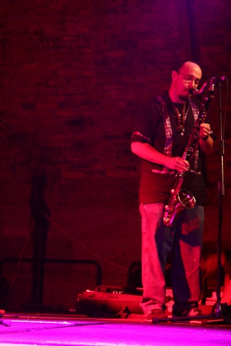A man in a patterned shirt playing a bass clarinet